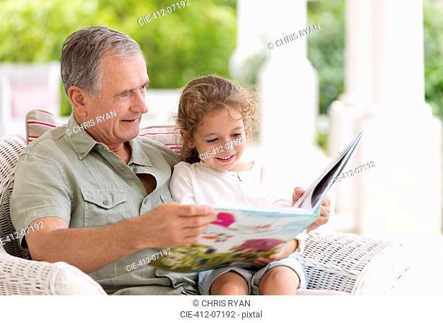 Older man reading to granddaughter on porch