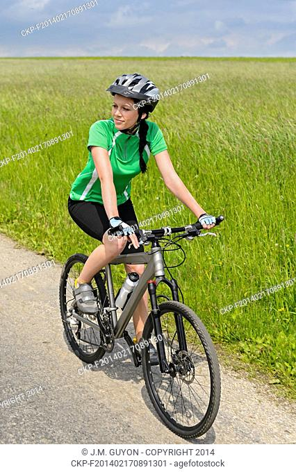 Woman riding her bicycle on countryside road sunny day
