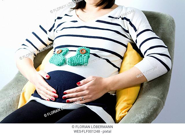 Pregnant woman sitting with baby's socks on belly