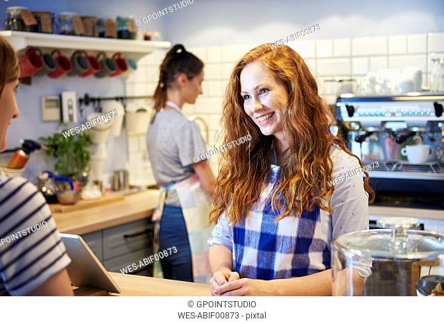 Smiling waitress talking to customer at counter in a cafe