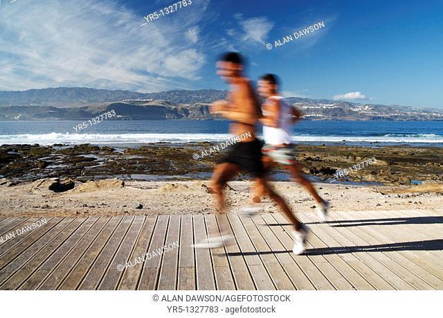Running on boardwalk at surfers beach, El Confital in Las Palmas, Gran Canaria, Canary Islands, Spain