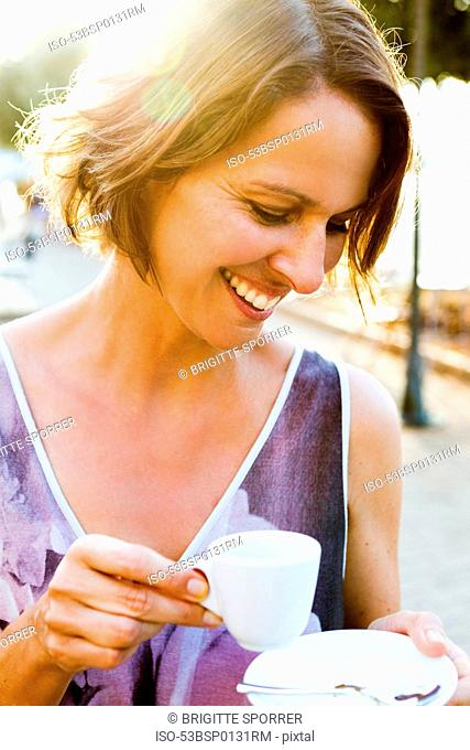 Woman having espresso outdoors