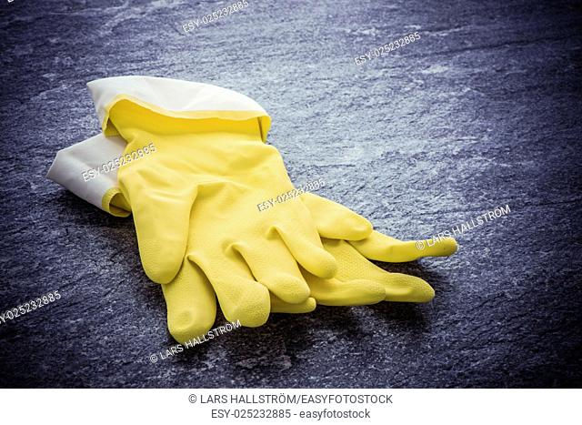 Yellow rubber gloves lying on stone surface. Image showing concept of cleaning, household work and protective wear