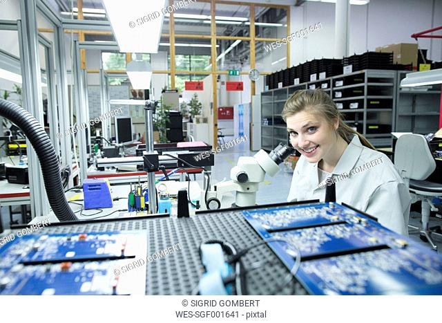 Portrait of smiling technician examining circuit board with microscope