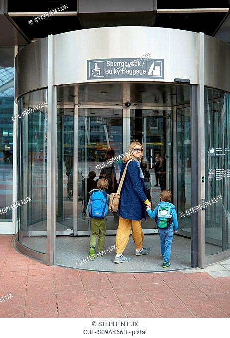 Rear view of mother and sons holding hand entering airport terminal