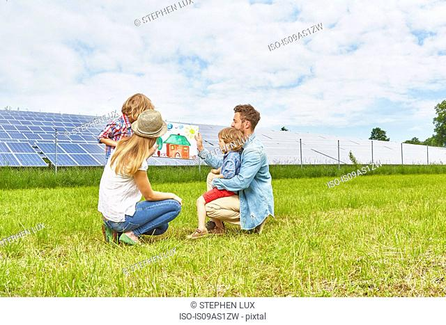Young family sitting in field, looking at child's drawing of house, next to solar farm