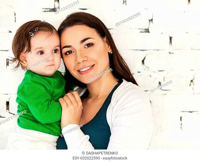 Happy smiling mother with eight months old baby near white brick wall