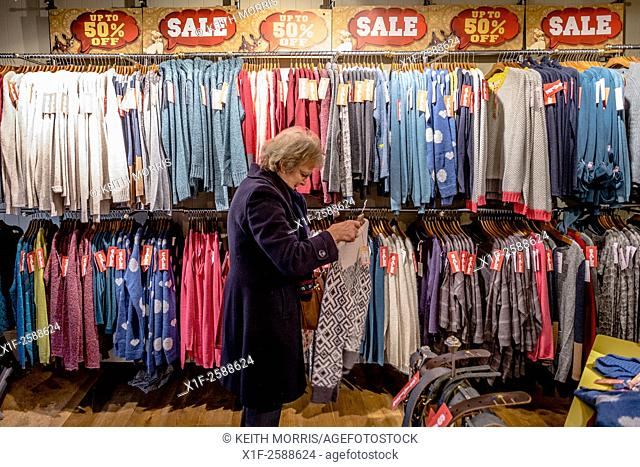Interior, boxing day sales: a woman shopping at White Stuff high street fashion clothing retail store UK