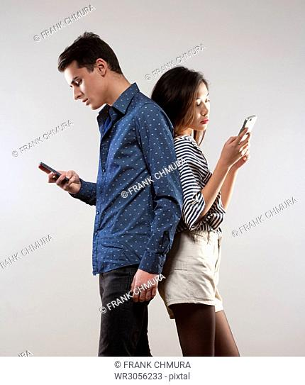 Portrait of a Teenage Couple with Smartphones Texting