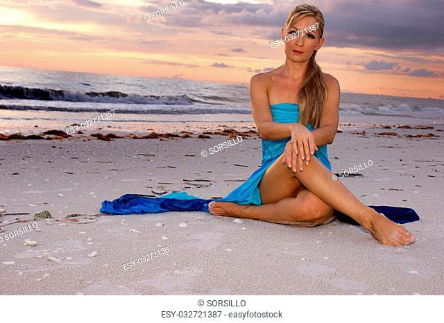 woman sitting cross legged on beach looking directly at the viewer, her legs are crossed and her hands are resting on her knees. with copy space
