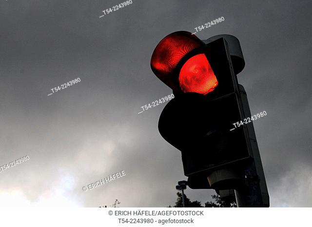 Red traffic light against a black sky