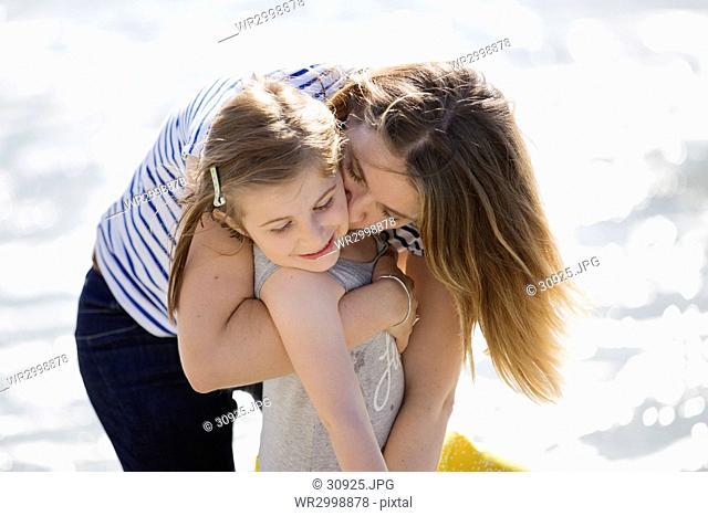 Blond woman wearing stripy T-shirt standing on beach, hugging girl