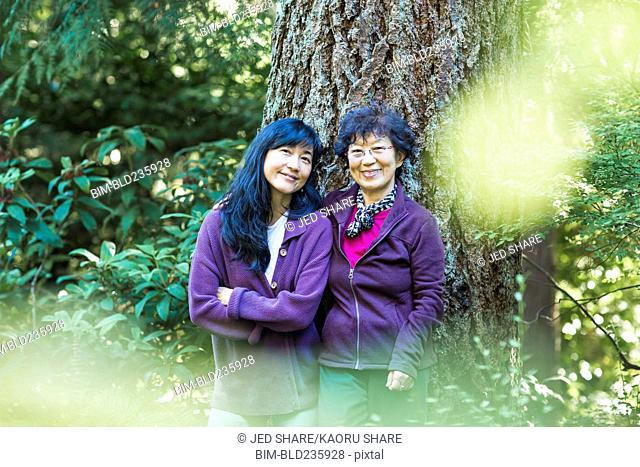 Smiling Japanese mother and daughter posing near tree trunk