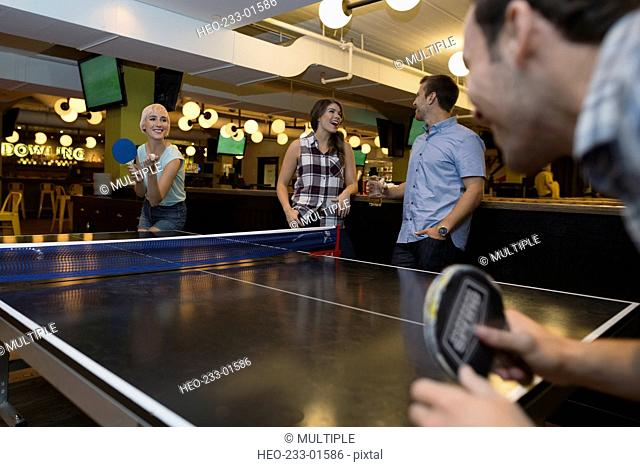 Friends playing ping-pong at bowling alley