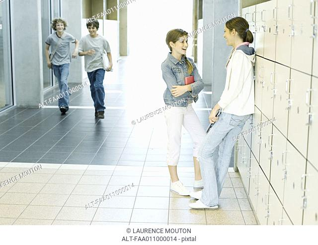 Two teen girls talking by lockers while boys run through hallway