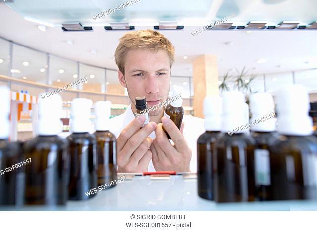 Young pharmacist choosing medicine