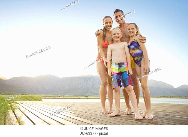 Family in swimwear on wooden jetty