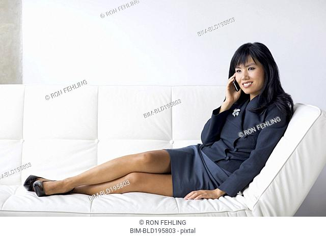 Asian businesswoman with feet up talking on cell phone
