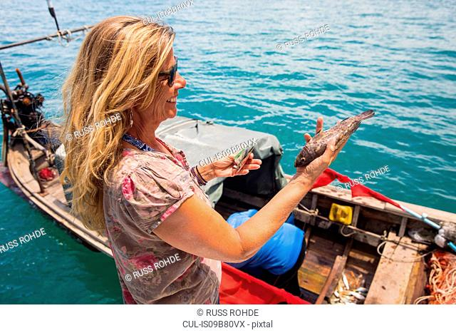 Woman holding fish by longtail fishing boat, Koh Yao Yai, Thailand, Asia