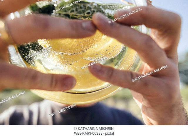 Detail of man drinking water infused with lemon and mint