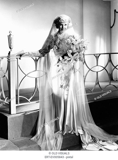 Young woman standing in wedding dress and holding a bouquet of flowers All persons depicted are not longer living and no estate exists Supplier warranties that...