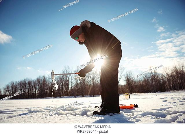 Ice fisherman digging hole in snow