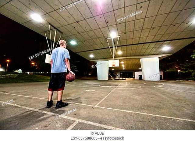 Young basketball player standing in outdoors covered court, ball in his hand and back to camera at night