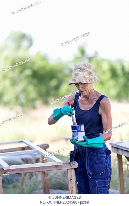 Mature woman painting window