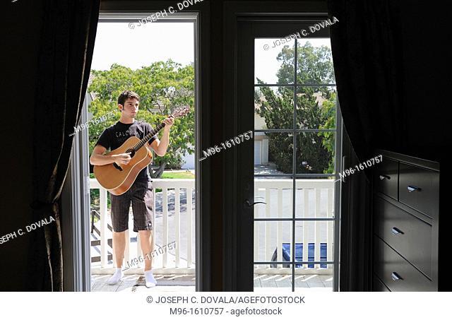 Young man playing guitar on balcony, Thousand Oaks, California, USA