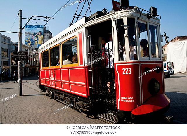 The old tram at Taksim Square and Turkcell cellular phone operator publicity placard . Istanbul. Turkey