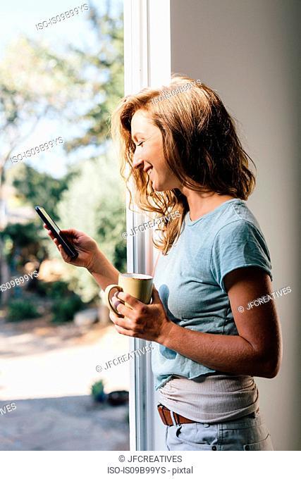 Happy young woman at patio door looking at smartphone