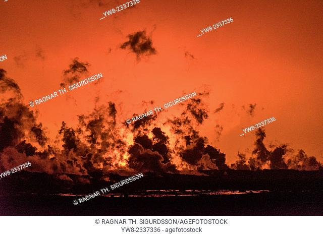 Steam rises from the lava flow at the Holuhraun eruption. The glow of the eruption lights up the sky in the background. Picture Date: September 20, 2014