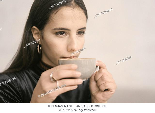 portrait of content woman sipping coffee, pensive, in Munich, Germany