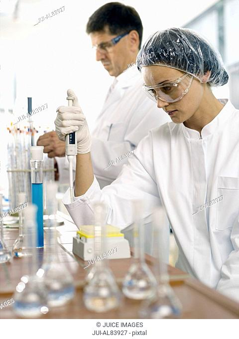 Female scientist using tester in laboratory