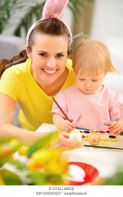 Mother and baby drawing on Easter eggs