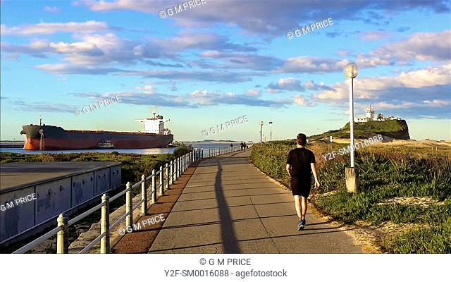 people walking as cargo ship enters harbour at Newcastle, Australia