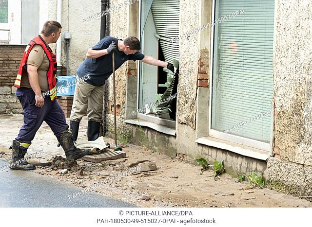 30 May 2018, Germany, Bad Gandersheim: Firemen standing next to a damaged window. The floods which occured after heavy rain on Tuesday evening in the...