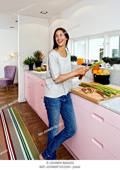 Scandinavia, Sweden, woman smiling while preparing food in kitchen