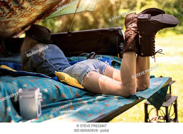 Young woman lying in pick up boot listening to music on radio