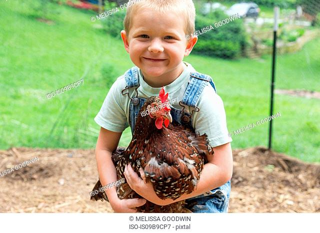 Boy holding speckled hen looking at camera smiling