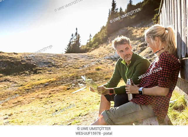 Hiking couple sitting in front of mountain hut, taking a break, holding map