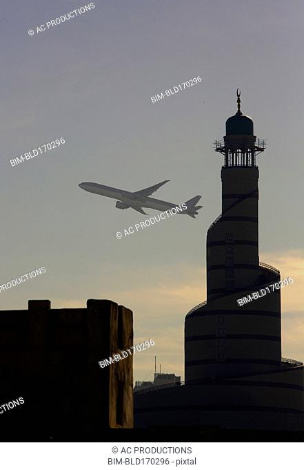 Airplane flying over Doha cityscape, Doha, Qatar