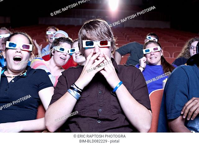 Friends watching movie in theater wearing 3D glasses