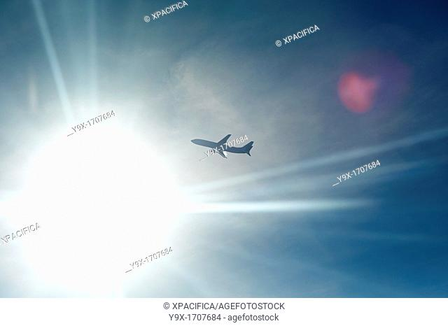 An airplane backlit by the sun in midair