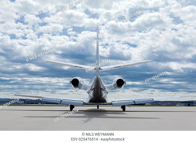 airplane private on the tarmac in front of the hangar in the summer with blue sky with clouds