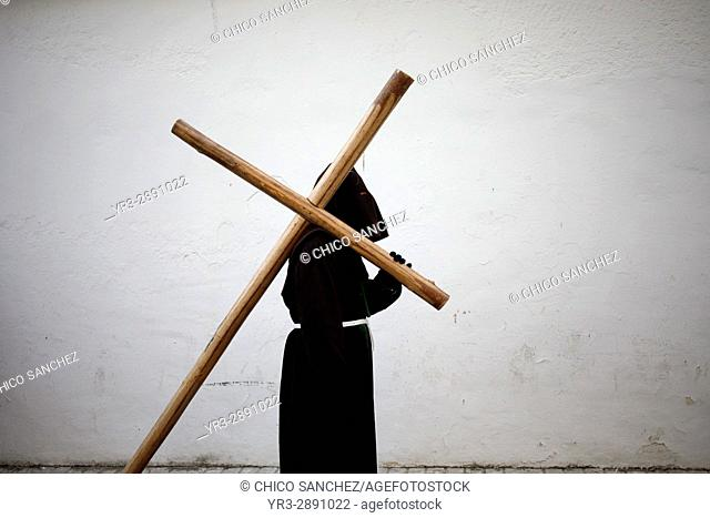 A hooded penitent carries a cross during Easter Week celebrations in Baeza, Jaen Province, Andalusia, Spain