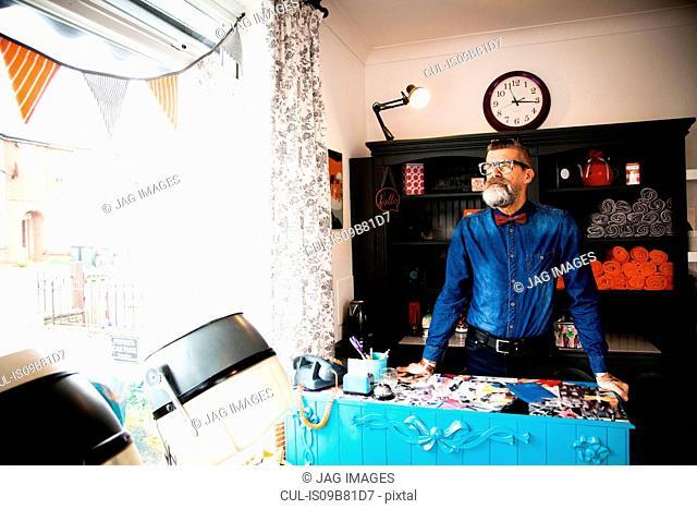 Man at reception desk of quirky hair salon