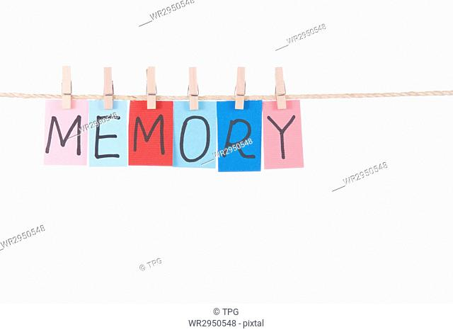 Memory, Colorful words hang on rope by wooden peg