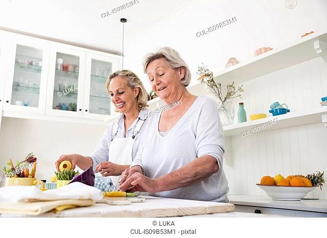 Senior woman and daughter preparing vegetables at kitchen table