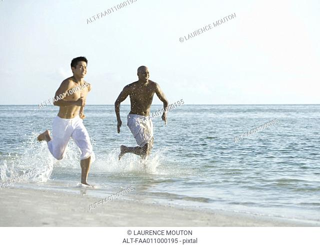 Two men running in surf